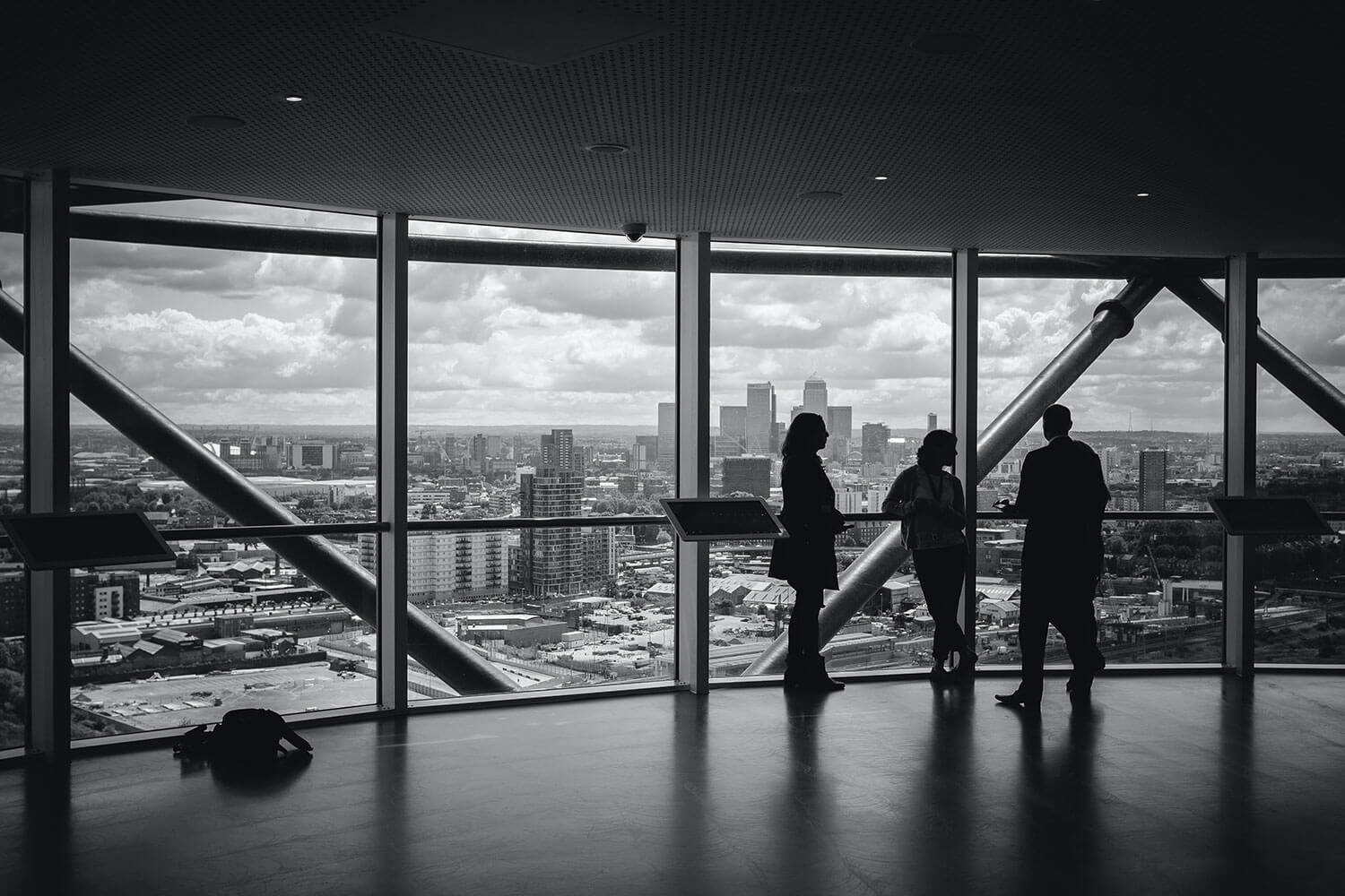 Silhouettes in front of a glass window in a city high rise