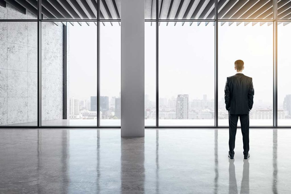 Business Man Staring Out Windows Over City Skyline